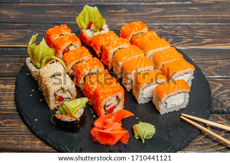 Beautiful and delicious varied sushi rolls on a stone board #1710441121
