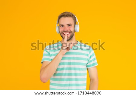 In music silence is more important than sound. Happy man make secret gesture. Guy listen to sound track in headphones. Sound and music technology. Stereo sound. Quiet please while music is playing. #1710448090