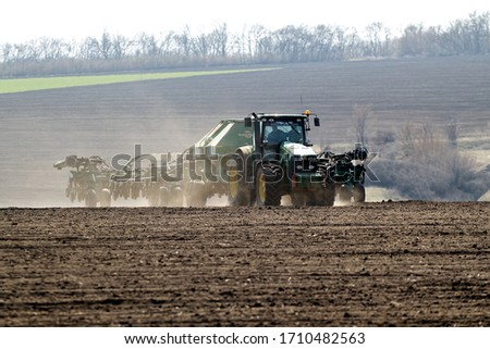 Kharkiv, Ukraine - April 10, 2019: Green tractor with trailed seeder working in field in a sunny spring day in Kharkiv Oblast, Ukraine on April 10, 2019 #1710482563
