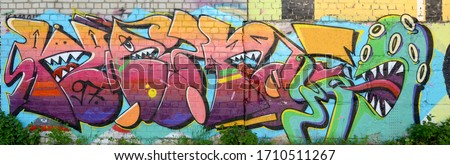 Abstract colorful fragment of graffiti paintings on old brick wall with scary octopus face. Street art composition with parts of unwritten letters and cartoon character Royalty-Free Stock Photo #1710511267