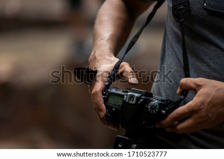 Close up hand and butterfly.  Professional photographer man holding camera for taking butterfly in the green jungle rain forest nature. Travel and Vacations Concept