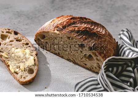 Authentic sourdough bread. Leavened bread. Sourdough starter. Whole wheat bread. Homemade. Piece of bread. Salted butter. Rustic organic bio product. Handcrafted product. Grey white backdrop. Slice #1710534538