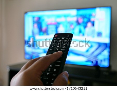 closeup of hand with the remote control television and presses the button. #1710543211