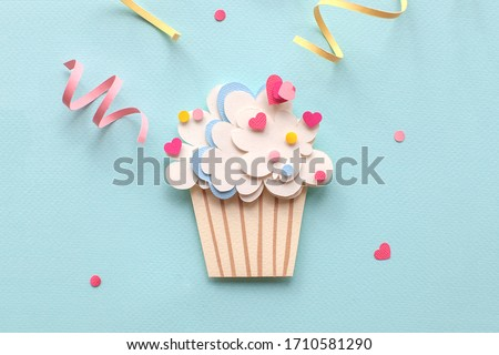 Handmade paper art and cutout cupcake on blue background. With colorful sprinkles. Cartoon style. Close up.