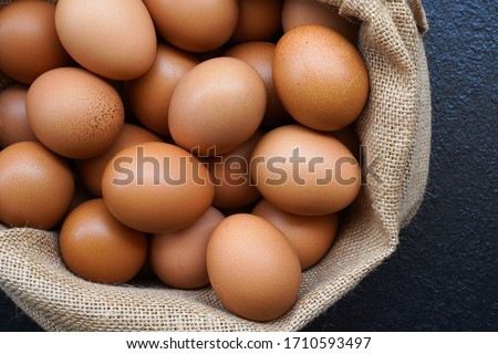 Chicken eggs in sack bag on black background. Royalty-Free Stock Photo #1710593497