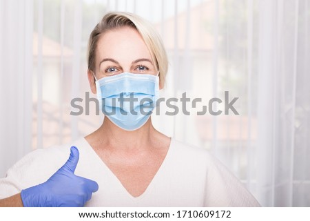 Woman wearing blue surgical mask and latex gloves giving thumbs up. Hospital environment. Healthcare concept. #1710609172