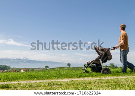 Father on the way with baby in buggy in beautiful springtime nature #1710622324