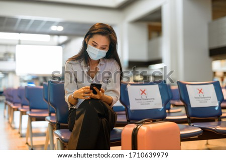 Young Asian tourist woman with mask using phone and sitting with distance at the airport Royalty-Free Stock Photo #1710639979