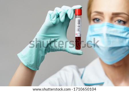 medical doctor nurse woman wearing protective mask and gloves - holding virus blood test #1710650104