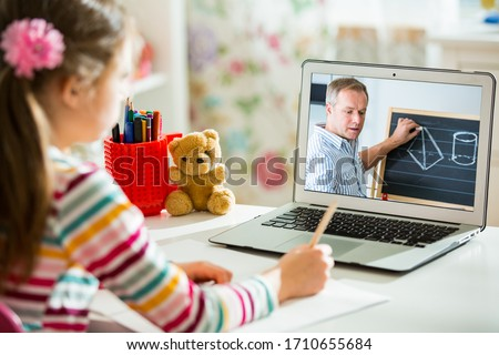 Middle-aged distance teacher having video conference call with pupil using webcam. Online education and e-learning concept. Home quarantine distance learning and working from home. Royalty-Free Stock Photo #1710655684