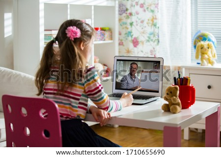 Middle-aged distance teacher having video conference call with pupil using webcam. Online education and e-learning concept. Home quarantine distance learning and working from home. #1710655690
