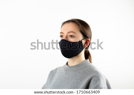 Portrait of young woman wearing black face mask isolated on gray background. Dust protection against virus. Coronavirus pandemic time. Female looking at camera #1710663409