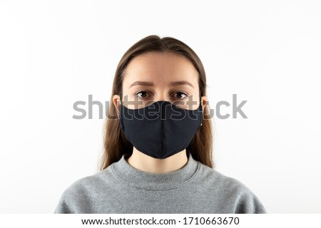 Portrait of young woman wearing black face mask isolated on gray background. Dust protection against virus. Coronavirus pandemic time. Female looking at camera #1710663670