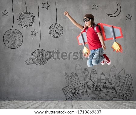 Happy child playing with toy paper wings. Kid pilot having fun at home. Success, innovation and space concept Royalty-Free Stock Photo #1710669607