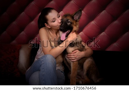 Lovely Portrait of the Cute Dog - German Shepherd Puppy and best friend Smiling, Young, Pretty Woman. Woman is Hugging and Cuddling a dog. The best friends concept. #1710676456