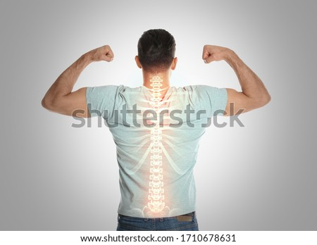 Man with healthy back on light background. Spine pain prevention Royalty-Free Stock Photo #1710678631