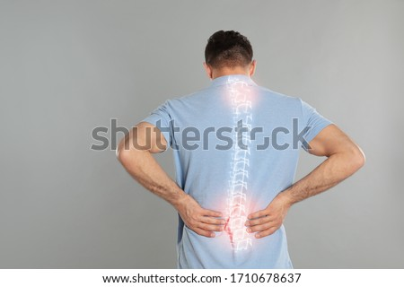 Man suffering from pain in spine on grey background Royalty-Free Stock Photo #1710678637