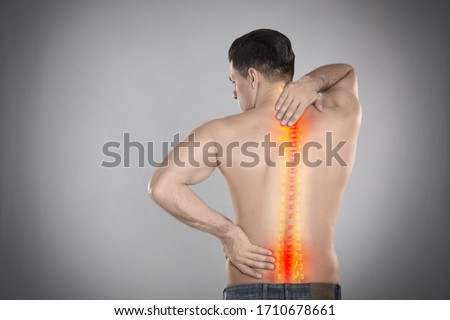 Man suffering from pain in spine on grey background Royalty-Free Stock Photo #1710678661