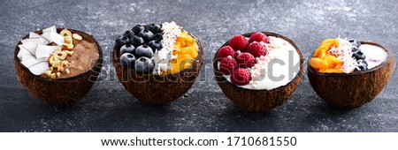 closeup four smoothie bowls with berries and fruit in coconut bowls on grey background for banner, trendy dessert