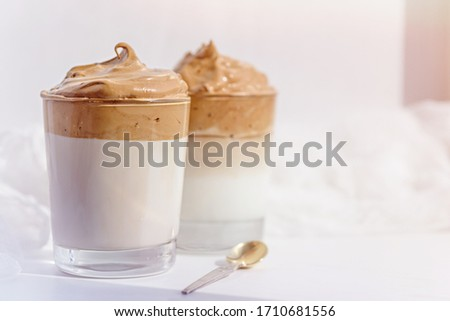 dalgona coffee with whipped foam in glasses on white background in morning light, korean coffee concept #1710681556