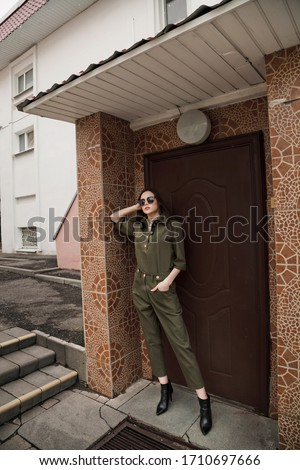 Caucasian fashion model in fashionable clothes wearing green pants suit. Fashion photo. Luxury clothes, street style. A stylish look in urban background. wide low angle view posing in the entrance