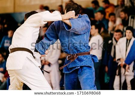 fight judokas on judo competition. background of fans tribune Royalty-Free Stock Photo #1710698068