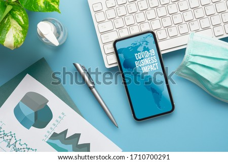 Coronavirus Covid-19 pandemic outbreak Business impact background concept. Mockup mobile phone with computer keyboard, business charts, facemask for Covid 19 financial business impact analysis  #1710700291