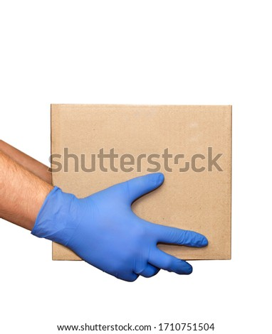 Hand in blue medical glove gives cardboard box.Concept of safety mail goods courier delivery in virus or coronavirus quarantine. Donation concept. Voluntary assistance to those in need.Volunteering #1710751504