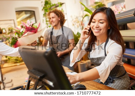 Saleswoman or florist takes order on the phone Royalty-Free Stock Photo #1710777472