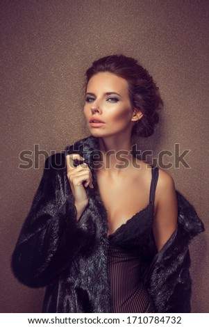 Beautiful sexy long-haired brunette woman in black lingerie and fur coat posing in the studio. The beauty of the face and body. Photos shot in a studio. #1710784732