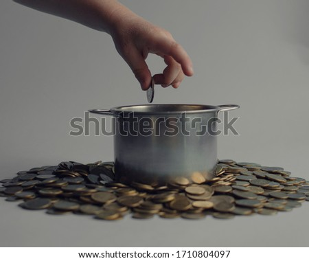 Hand of a child throwing money into a pot which stands on a pile of money. #1710804097