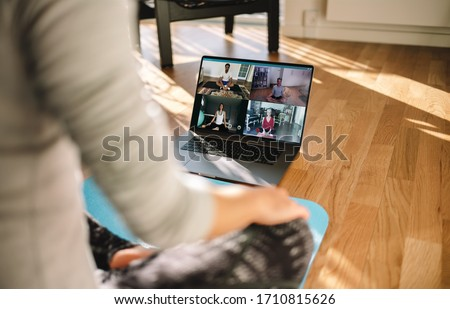 Group of people practicing yoga with trainer via video conference. Fitness coach teaching yoga online to group of people. #1710815626