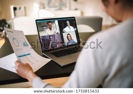 Woman holding a business report working at home having a video conference with colleagues. Over the shoulder view of a businesswoman having online business meeting from home. #1710815632