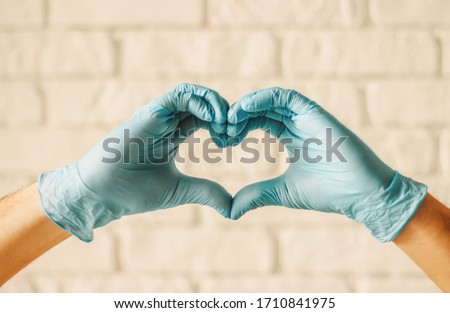 Men hands in protective gloves showing heart symbols in hospital. Doctor surgeon in medical gloves gesturing love sign with fingers. Arms in heart shape. Health care, charity, COVID-19 protection #1710841975