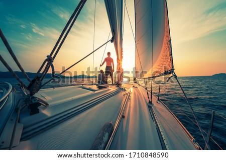 Young couple sailing on the boat at sunset Royalty-Free Stock Photo #1710848590