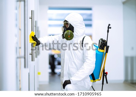 Cleaning and disinfection of office to prevent COVID-19, Man in protective hazmat suit washes office furniture to preventing the spread of coronavirus, pandemic in quarantine city. #1710905965