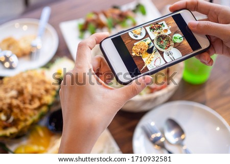 The girl's hand is taking pictures of the food on the table at home after ordering food online to eat at home. The concept of mobile phones to order food online