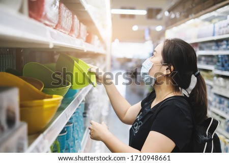 asian woman wearing protective mask and bag pack, to protect from surrounding airborne transmission of corona virus COVID-19 disease, in supermarket shopping to stock produce for short term isolation #1710948661