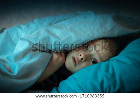 boy in bed with his eyes open. the child is afraid of the dark. tormented by nightmares and terrible dreams in children #1710963355