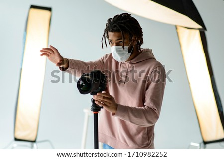 Photographer with medical mask.  man in photography studio.