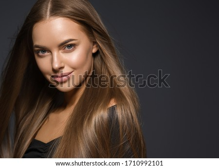 Beautiful woman smooth long hair brunette natural make up tanned skin beautiful female portrait over dark background Royalty-Free Stock Photo #1710992101