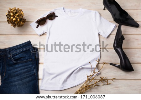 White cotton T-shirt mockup with black high heels pointed toe women pumps and golden plants. Design t shirt template, tee print presentation mock up Royalty-Free Stock Photo #1711006087