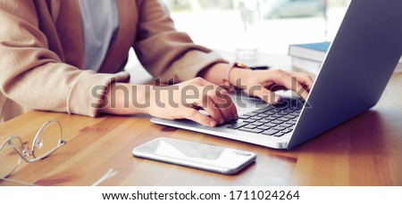 Young woman working on computer at table in office, closeup. Banner design