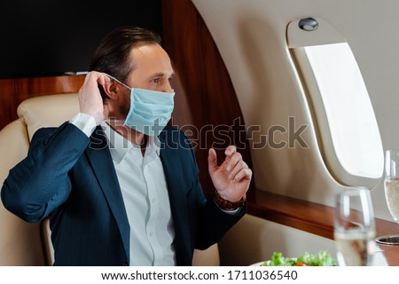 Selective focus of businessman putting on medical mask near champagne and salad on table in airplane #1711036540