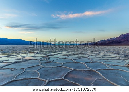 Badwater Basin at Sunset. Salt Crust and Clouds Reflection. Death Valley National Park. California, USA