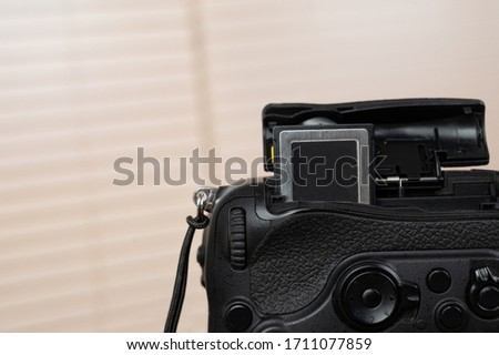 memory card, digital camera, dslr and body black camera placed on a wooden table