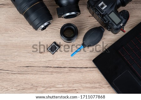 Black laptop and accessery of digital camera dslr on the wooden table