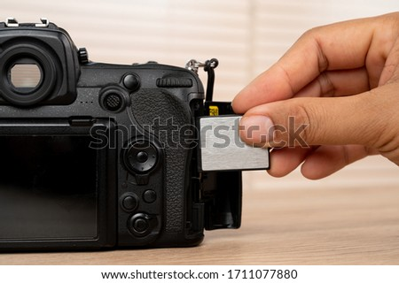 The photographer's hand captures memory. black dlsr digital camera card inserted in the slot of the camera