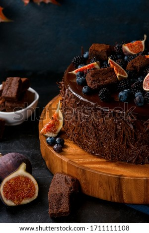 Chocolate cake with figs, blueberries, blackberries and brownie on wooden board on black table on blue background with autumn leaves. Closeup. Royalty-Free Stock Photo #1711111108