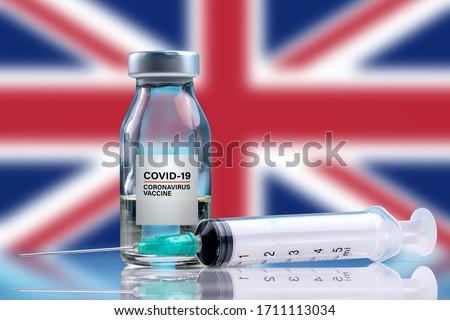 Vaccine and syringe injection. For prevention, immunization and treatment from corona virus infection (novel coronavirus disease 2019, Covid-19). England Flag background. Royalty-Free Stock Photo #1711113034
